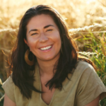 Tara in a field with earth-tone clothing.