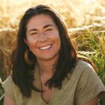 Tara, wearing earth-tone clothing in a field.