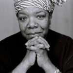 Maya Angelou in a dark shirt with her chin in her hands, smiling.