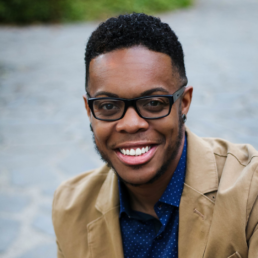 photo of Kyle, smiling in glasses, a snappy tan blazer and a navy blue button down with a small white pattern