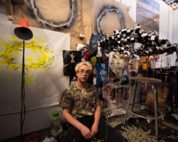 Oliver in the art studio, surrounded by lamps and works in various mediums